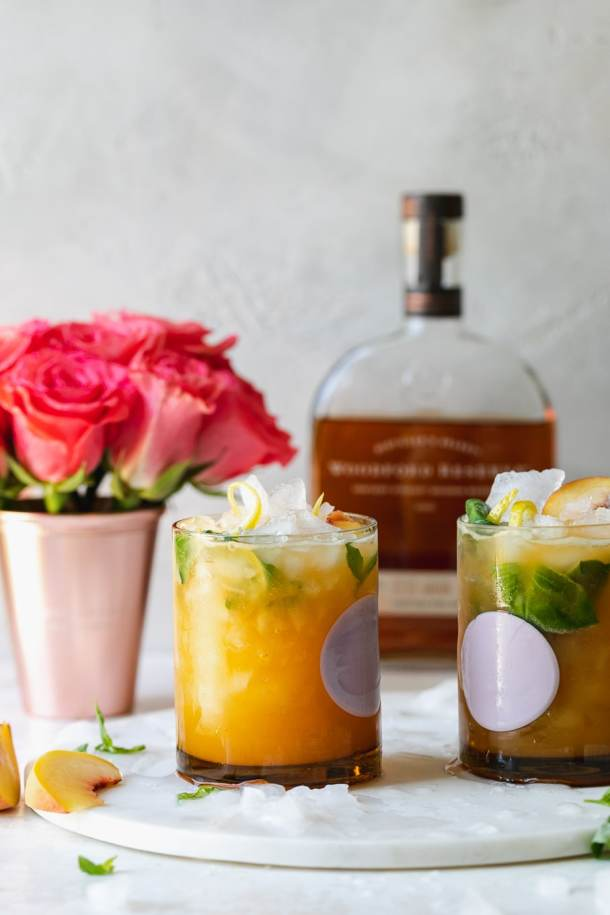 Straight on shot of cocktails with roses and a bottle of bourbon