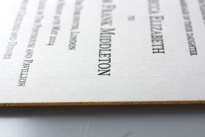 thermographed invitation with gilded edge in gold