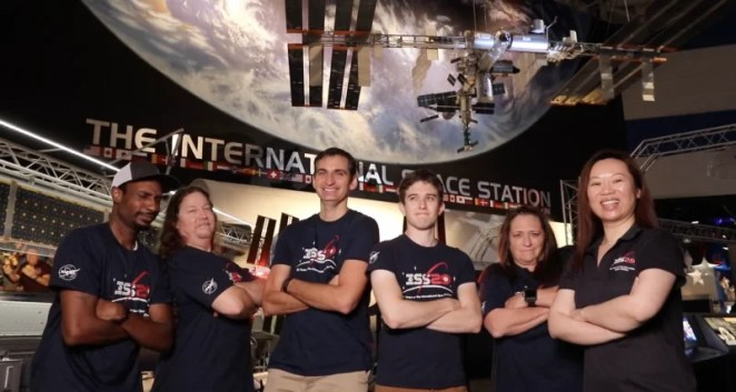 Team ISS posing in NASA t shirts in front of the ISS mimic