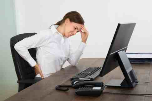 45461237 - young businesswoman suffering from backache and headache in office