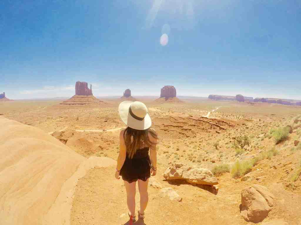 girl with sunhat standing at monument valley