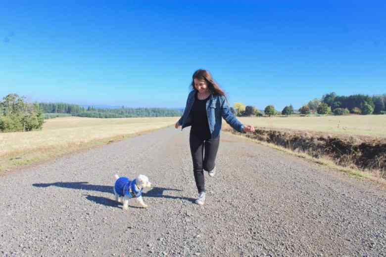 girl and dog run down country road