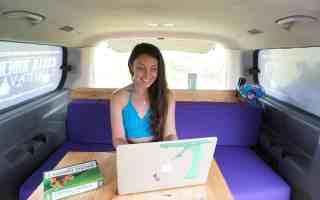 girl on laptop in camper van