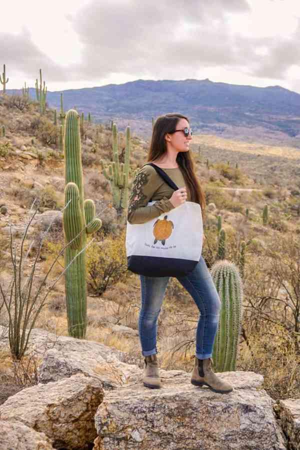 girl wearing sea turtle tote bag in desert