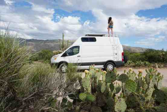 Girl on van in desert with cacti