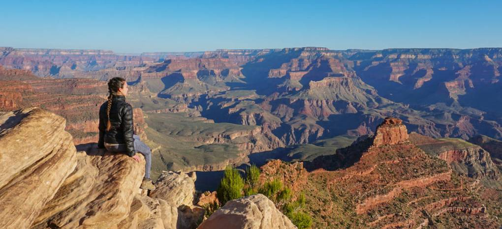 girl sitting at ooh aah point at grand canyon