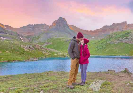 couple kissing at ice lake basin at sunset