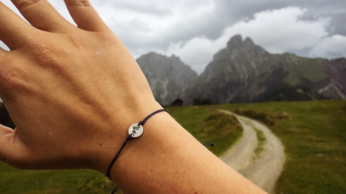 Eine Hand mit einem Bergarmband vor Berge