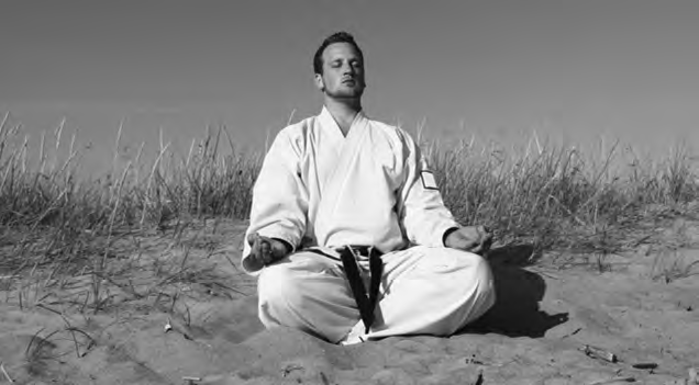 "Black-belt karateka in ""gi"" (karategi) meditating in yoga ""lotus"" position"