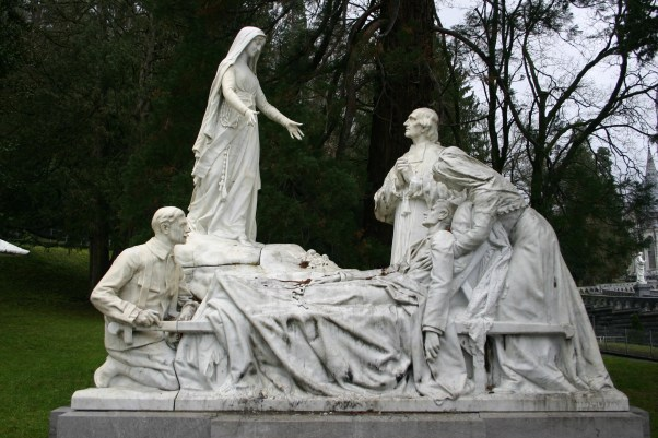 Statue at Lourdes Shrine of Mary appearing to man in bed