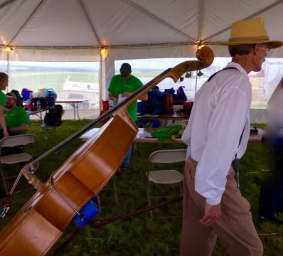 A musician from the Tallgrass Express String Band, which performed earlier in the day, walks through the crowd with instrument in tow. (photo by Bob Sessions)