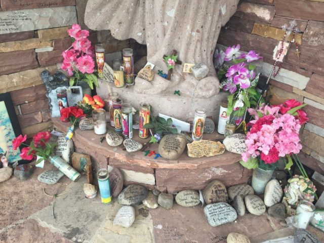 Offerings left at the base of a statue to the Virgin Mary at Chimayo. (Bob Sessions photo)