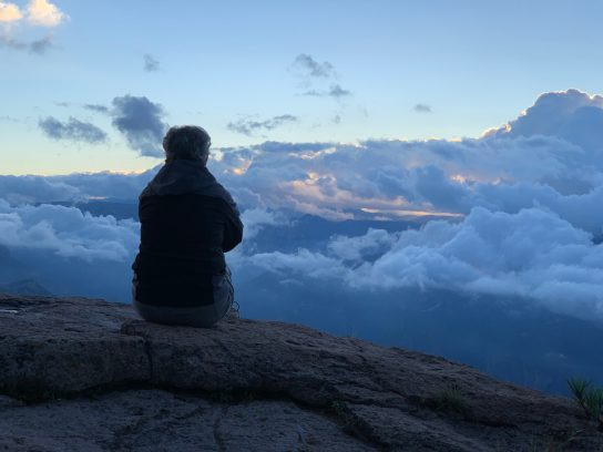 woman on mountain overlooking clouds, seated figure on mountain top, mountain with clouds,