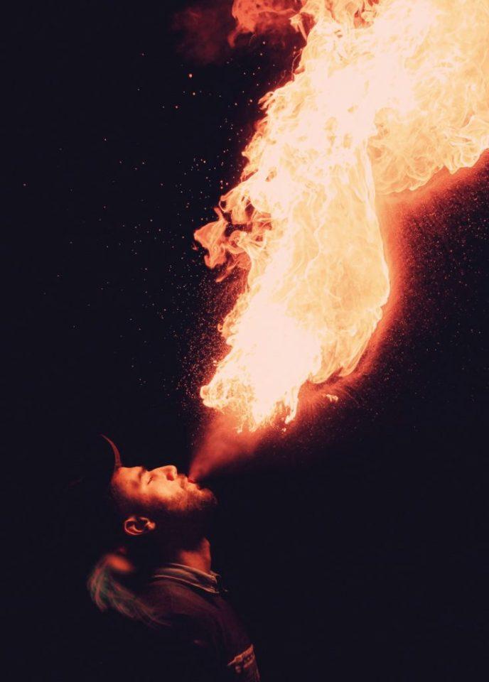 vuurshow, een man die vuur spuugt