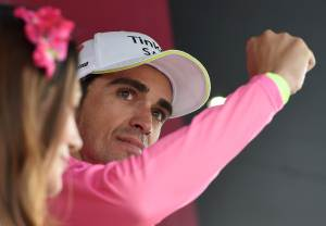 The overall leader Spanish rider Alberto Contador of the Tinkoff-Saxo team reacts wearing the pink jersey  on the podium following the 16th stage of the 98th Giro d'Italia cycling tour over 177 km from Pinzolo to Aprica, 26 May 2015. ANSA/DANIEL DAL  ZENNARO