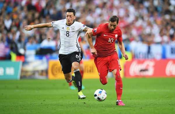 Mesut Özil (Deutschland) und Elfer-Sieg-Torschütze Grzegorz Krychowiak (Polen) – Fussball EM 2016: Aktion während der UEFA EURO 2016 Gruppe C - Spiel zwischen Deutschland und Polen im Stade de France am 16. Juni 2016 in Paris, Frankreich. Foto: Getty Images