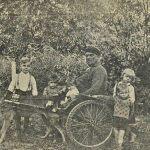 Инвалид в коляске с запряженным малинуа, в окружении своих детей