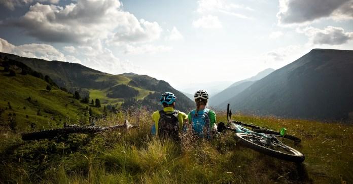Biker geniessen die Aussicht während ihrer Pause auf ihrer Tour durchs Val di Fiemme.