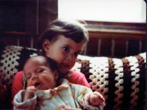 My sister holding me as a baby. I made that same face in every photo for at least the next four years.
