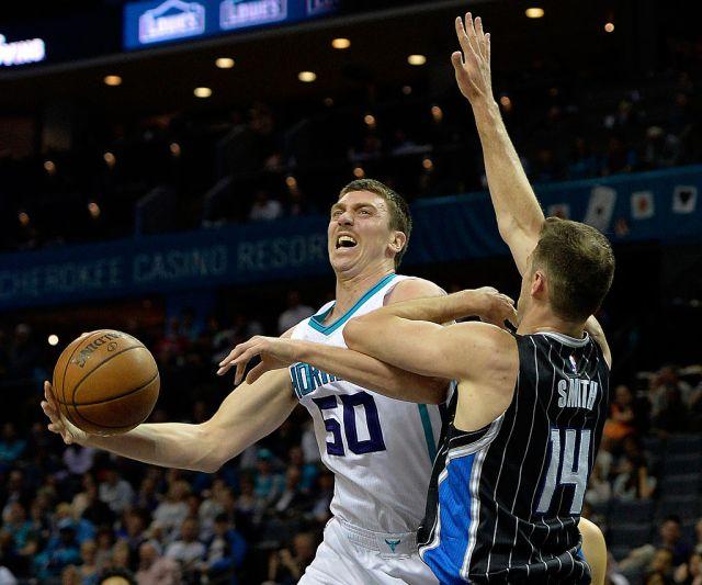 Jason Smith of the Orlando Magic fouls Tyler Hansbrough of the Charlotte Hornets.