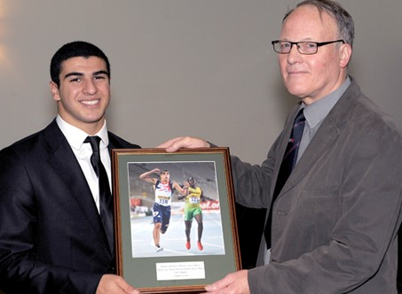 Sprinter Adam Gemili being presented with a framed image as his award as the top men's junior athlete in 2012 by the BAWA's chairman, Sandy Sutherland