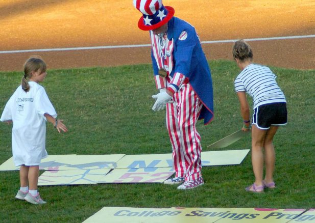 """Sammy"" helps two young contestants during a between-innings contest. Rob Jonas/Spotlight"