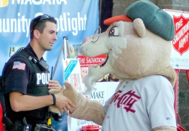 """Pappy Paw"" shakes hands with a police officer. Rob Jonas/Spotlight"