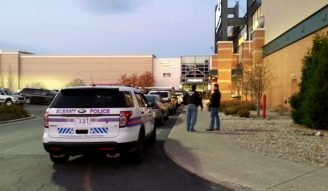 A pair of police officers stands outside the entrance to Dick's Sporting Goods at Crossgates Mall Saturday afternoon.