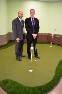 The Grand Guilderland Administrator Josh Gurock (left) and Regional Administrator Bruce Gendron standing on the facility's recently installed three-hole therapeutic putting green // Photo provided