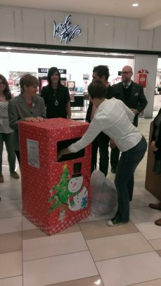 Erika Kutil of Best Cleaners donates a coat to the collection box outside Lord & Taylor // Photo courtesy of Albany County