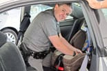 Trooper installing a child safety seat