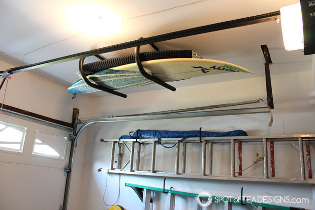 Take a tour of a clean and organized garage complete with resources on products used. Surfboard rack fits above the garage door! #organization #garage #mancave | spotofteadesigns.com