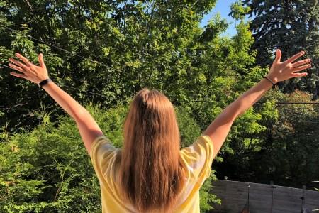 Femme de dos portant un t-shirt blanc à motif tie-dye jaune sur un fond d'arbres verdoyants en été.