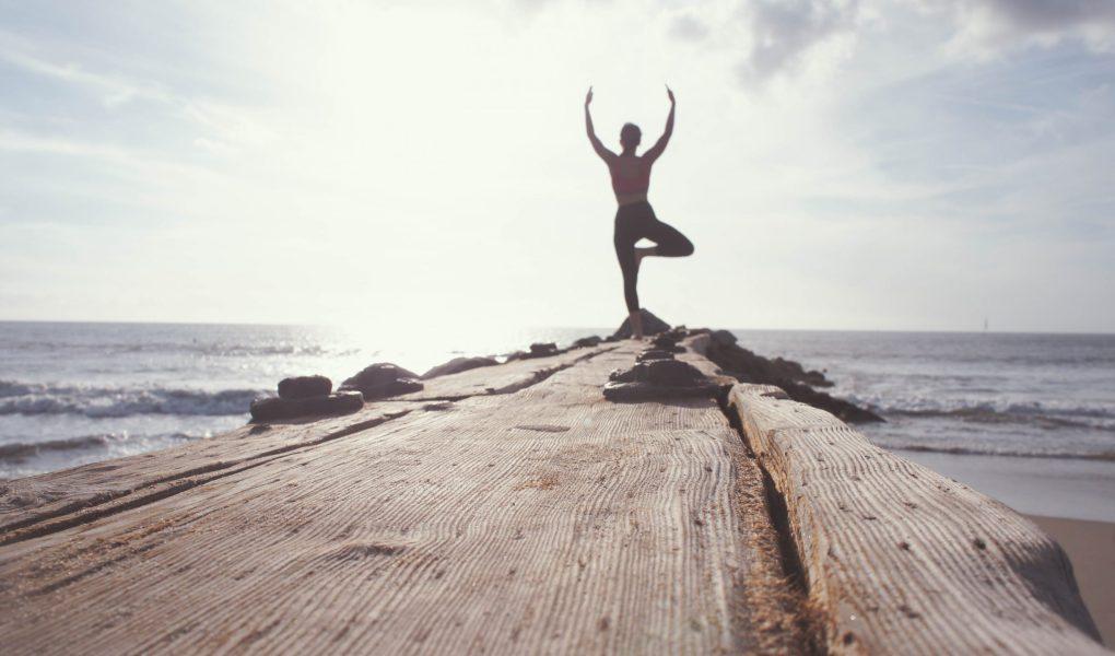 Femme prenant la position de l'arbre, face au soleil, au bord de la mer.