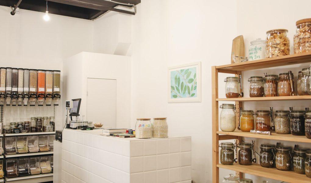Vue d'une boutique d'aliments en vrac : comptoir caisse, distributeurs à produits et étagère contenant plusieurs bocaux.