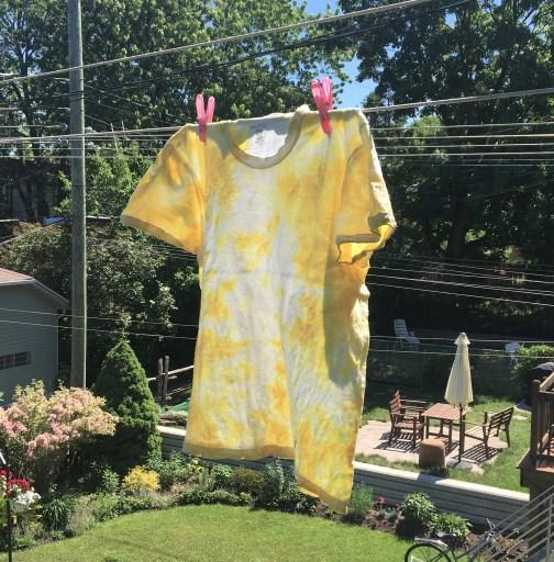 T-shirt à motif tie-dye jaune accroché sur la corde à linge sur fond d'arbres en été.