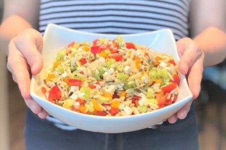 Personne tenant devant elle un bol de service rempli de salade d'orzo, une recette d'été colorée.