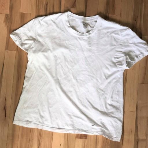 T-shirt blanc standard, étendu sur le plancher de bois.
