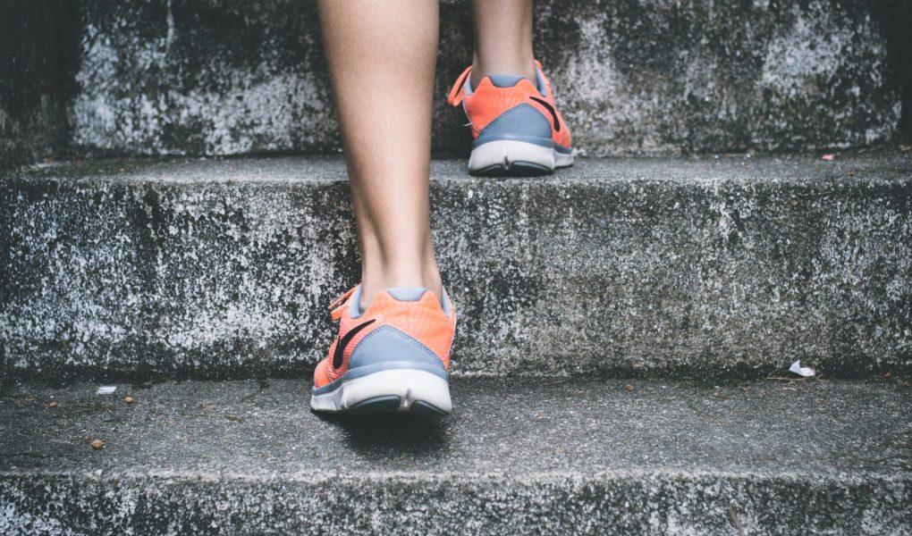 Pieds portant des espadrilles de course grise et orange et montant un escalier en pierre.