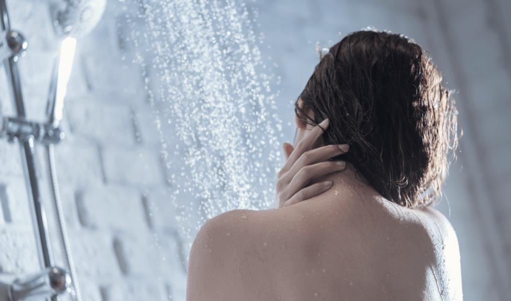 Femme qui prend sa douche, de dos.