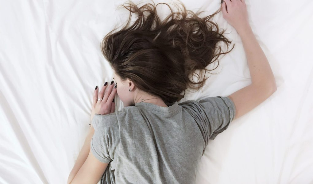 Femme endormie et allongée sur le ventre, légèrement de côté, sur une couette blanche.