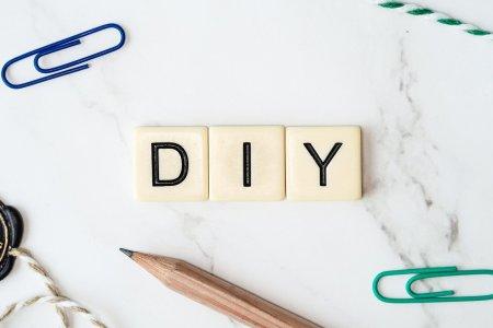 DIY (Do It Yourself) écrit avec des cases de jeu de société, sur fond de marbre, avec des articles de bricolage autour.