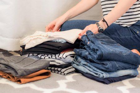 Personne assise en tailleur et encerclée de pile de vêtements.