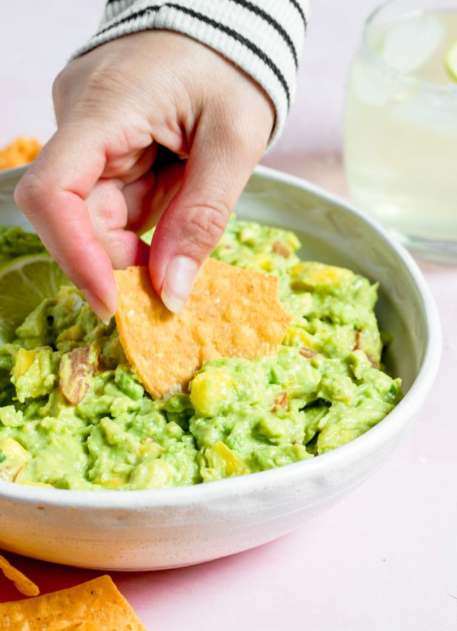 Chip dipped into spicy pineapple guacamole