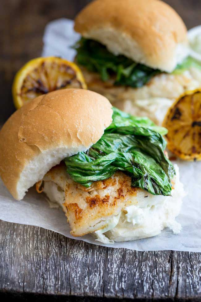 Crispy fish with a delicious tarragon mayonnaise and sweet charred lettuce, all served in a soft white bread roll. This fish burger is a flavour explosion and the perfect way to enjoy fish. And ready in under 15 minutes! From www.sprinklesandsprouts.com