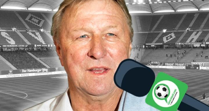 Horst Hrubesch mit dem spruchball Mikrofon und dem HSV Stadion im Hintergrund