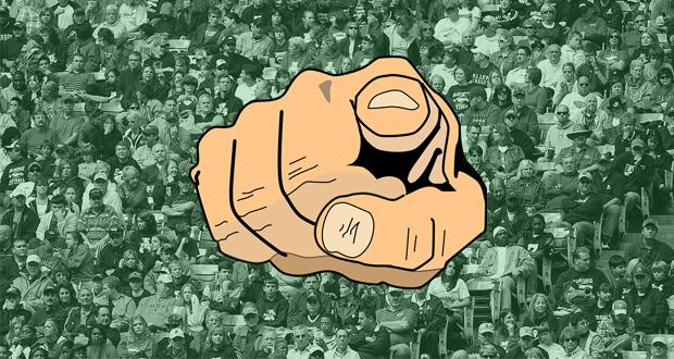 Ein Zeigefinger der direkt auf dich zeigt und Fußball Fans im Hintergrund