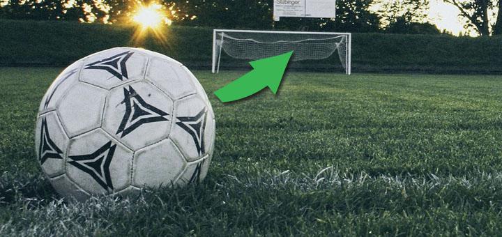 Ein Fussball am Rasen. Ein Pfeil zeigt auf das dahinter liegende Tor.
