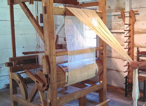 Beaming the warp on the loom in the Old Garrison House in Chelmsford, MA.