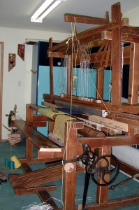 """60"""" 12-shaft loom built by Andeas Kohmann in Bamberg, Germany. Side view shows automatic take-up system."""